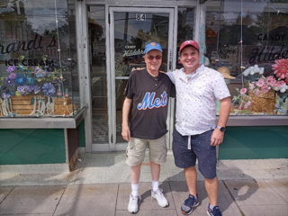 Two men standing in front of a store  Description automatically generated with low confidence